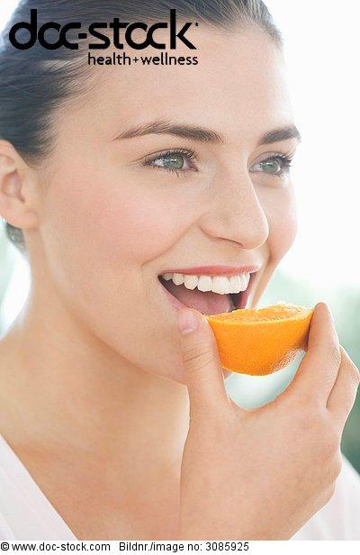 Junge Frau ein Stück Orange Essen