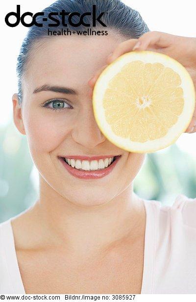 junge Frau hält up halbe grapefruit