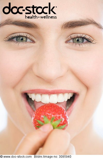 Junge Frau, eine Erdbeere in den Mund