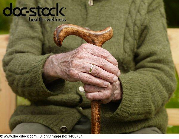 Senior hält Hände an Stock, close-up