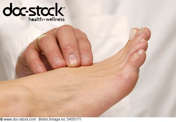 Doctor taking pulse at patient's foot