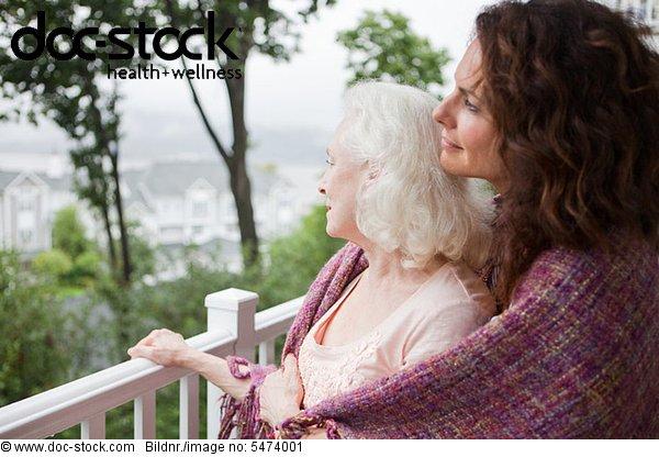 Seniorin und Tochter umarmen sich auf der Veranda