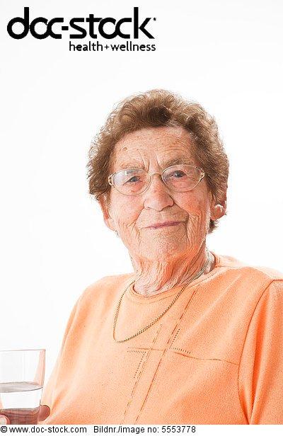 Lächelnde alte Frau mit Brille hält ein Glas Wasser, Portrait