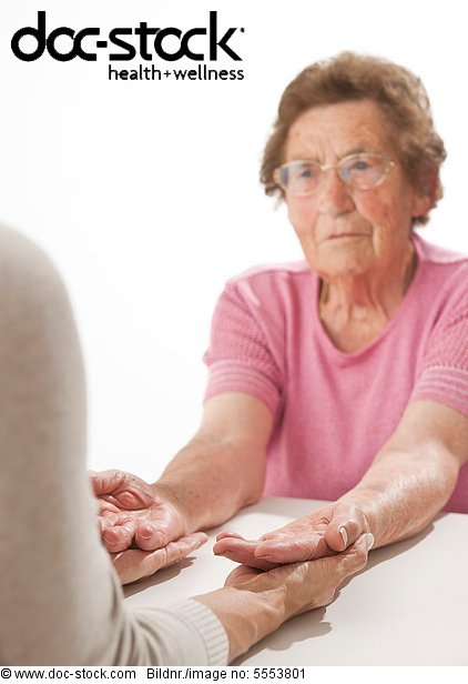 Reife Frau hält die Hände einer alten Frau