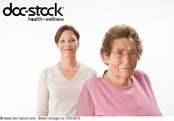 Ernste alte und lächelnde reife Frau