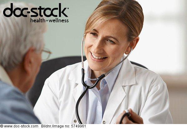 Arzt, der den Blutdruck des älteren Mannes nimmt.