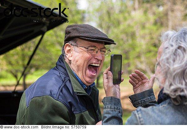 Seniorenfrau beim Fotografieren von Männern im Freien