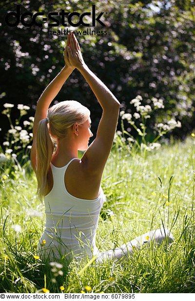Eine junge Frau praktizieren Yoga außerhalb
