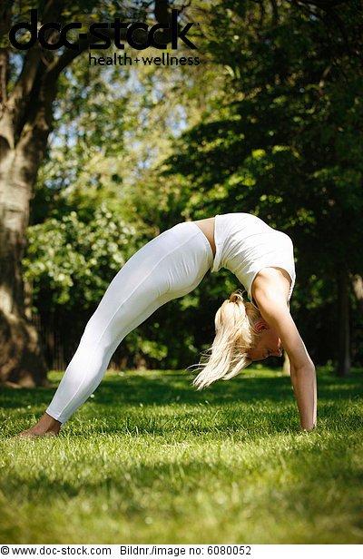 Eine junge Frau praktizieren Yoga outside, Rad poser