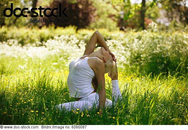 Eine junge Frau praktizieren Yoga außerhalb, pose Taube