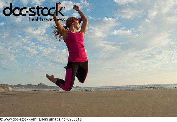 Junge Frau beim Springen in der Luft am Strand