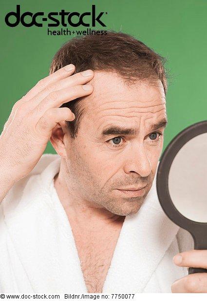 Mann im Bademantel schaut in einen Kosmetikspiegel