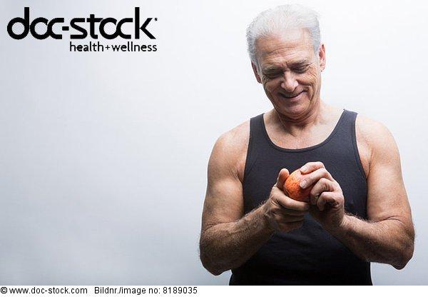 Senior Mann mit Apfel, lächelnd