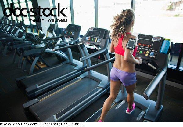 Junge Frau auf dem Laufband im Fitnessstudio