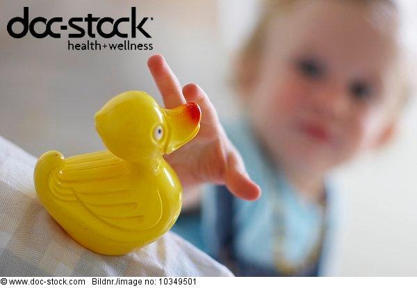 baby grabbing yellow rubber duck