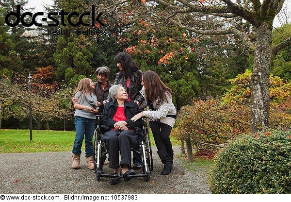 Mehrgenerationen-Familie mit Seniorin im Rollstuhl