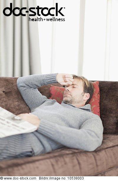 Mann mit Kopfschmerzen auf der Couch liegend