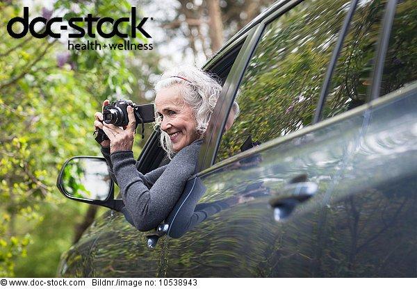 Seniorin fotografiert Mann Auto
