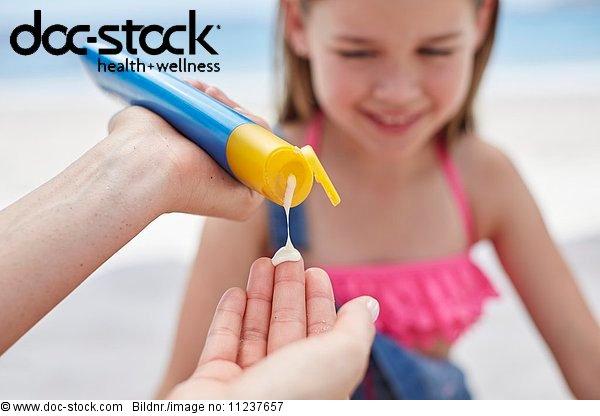 Person applying sun cream to a girl
