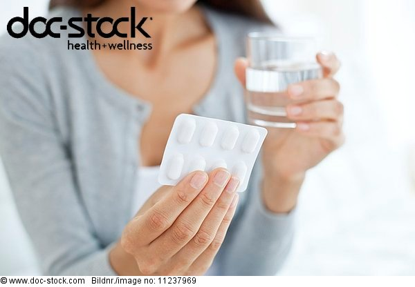 Young woman holding blister pack