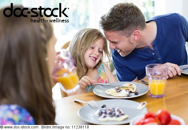 Father and daughter smiling at breakfast