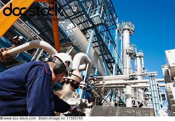 MODEL RELEASED. Worker checking pipework on an oil and gas refinery.