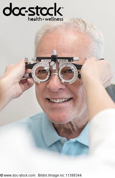 60 bis 70 Jahre,60-70 Jahre,anziehen,Arzt,Augenarzt,Augenheilkunde