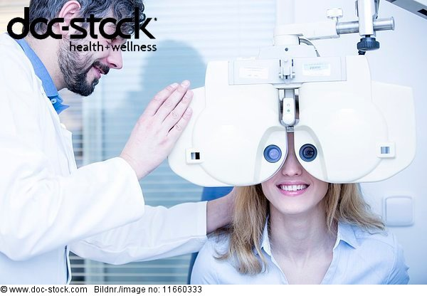 Young woman having eye exam performed by Optometrist.