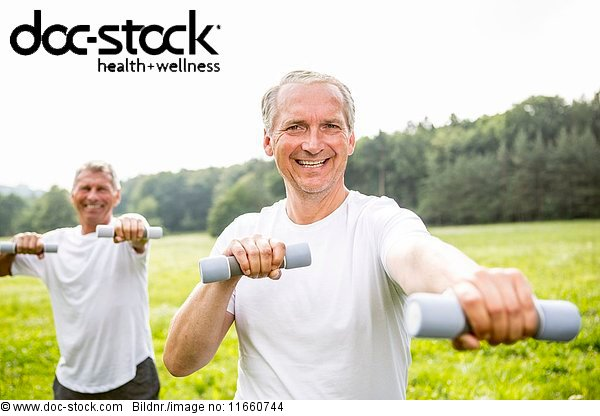 Two men exercising with hand weights.